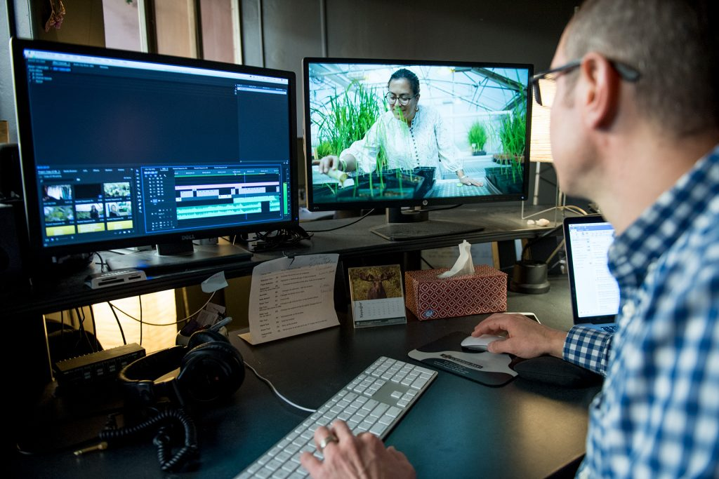 A video producer edits video in his office.