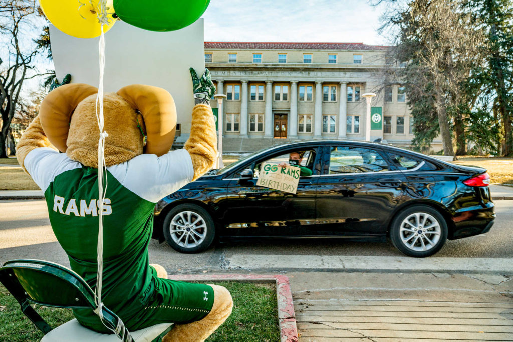 """Brian Dusek in his car holds sign out the window that says """"Go Rams, it's your birthday"""" while passing by CAM the Ram on the Oval."""